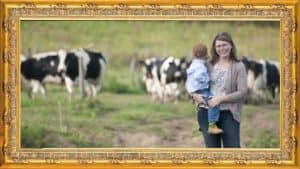 Woman holding kid by Holstein cows in framed picture