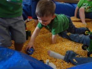 Kids playing in sandbox made of corn