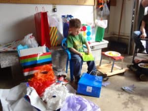 kid opening presents at birthday party