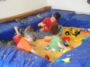 Kids enjoying playing with farm toys in corn pit at a birthday party