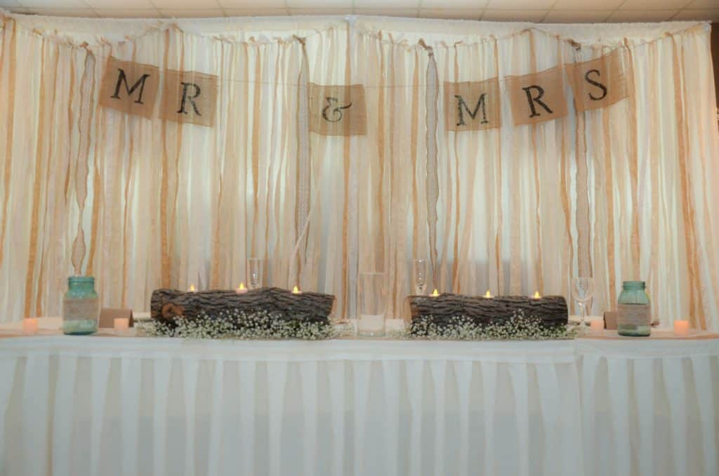 mr and mrs burlap banner behind head table at wedding reception