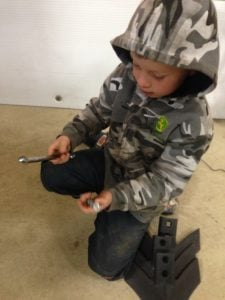 farm kid with machinery parts in shop