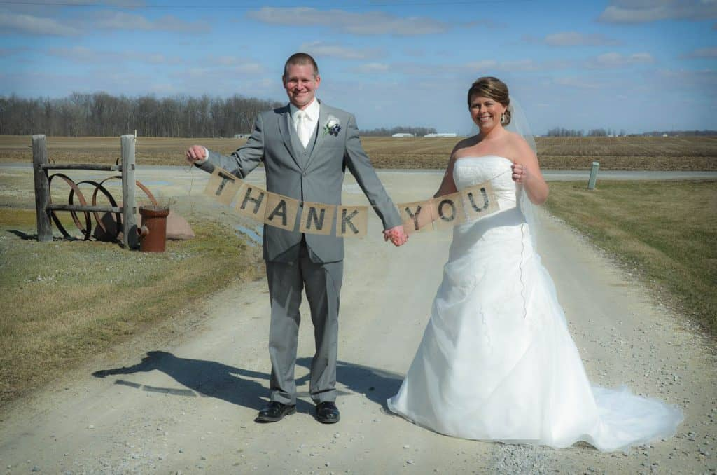 bride and groom holding thank you for banner