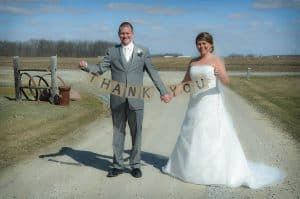bride and groom holding burlap thank you sign on a string