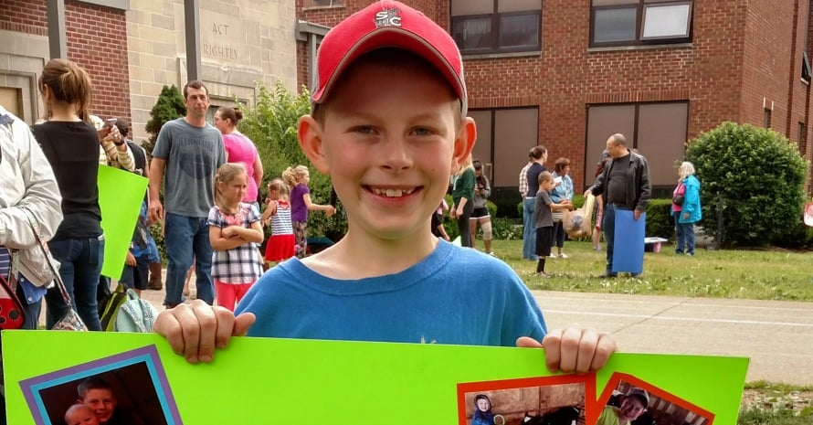 Smiling kid graduating third grade holding a poster
