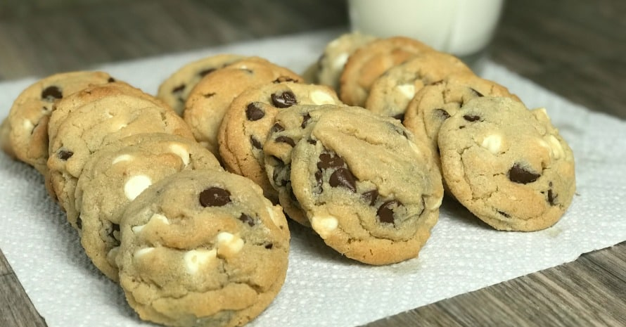 milk chocolate and white chocolate chips in cookies by a glass of milk on a paper towel