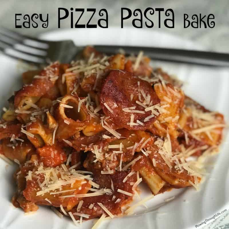 Pile of pepperoni pizza pasta bake topped with sauce and parmesan cheese on a white plate