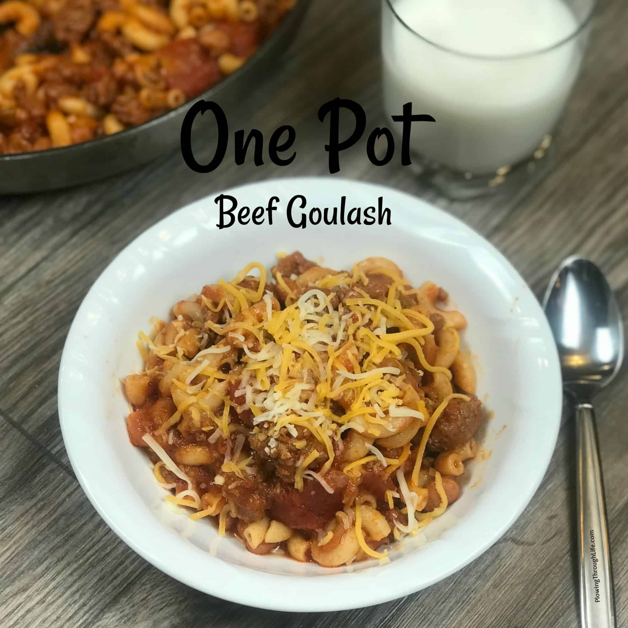 bowl of one pot beef goulash with shredded cheese