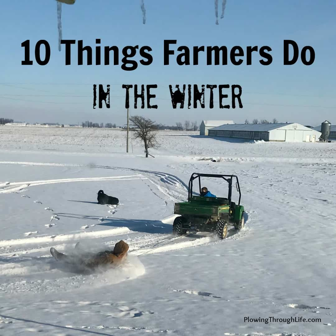farmer in the winter pulling a sled with a john deere gator