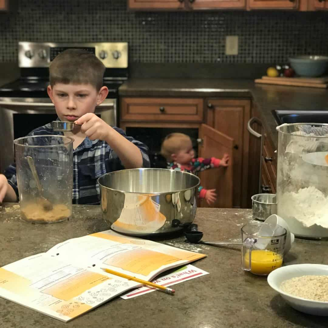 little farmer measuring brown sugar in kitchen