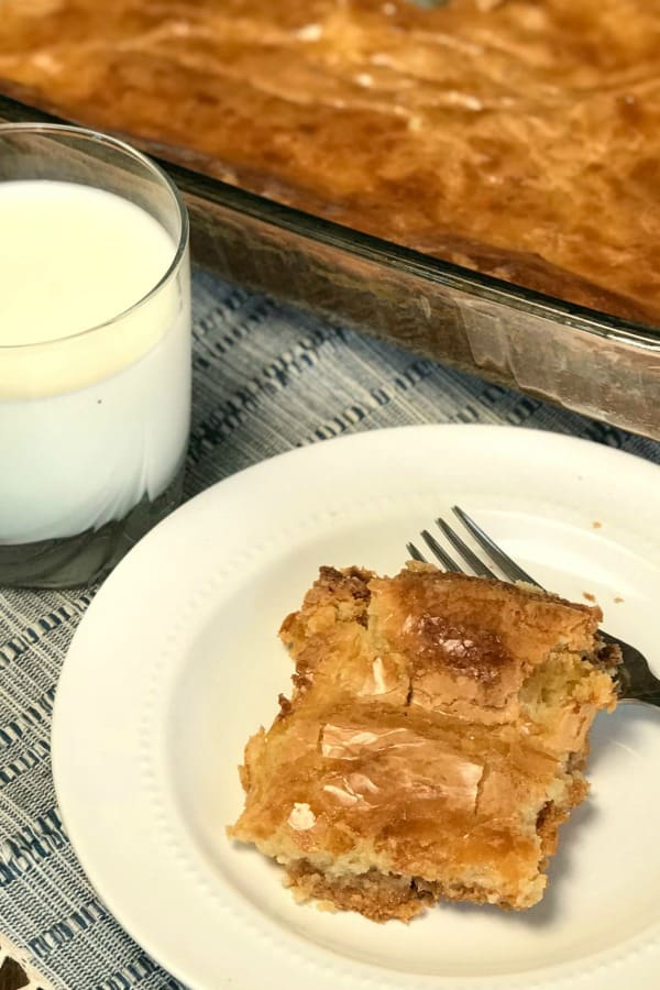 Piece of gooey butter cake on plate next to glass of milk and pan of cake.