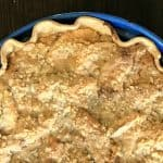 half of a streusel covered apple pie in a blue pan