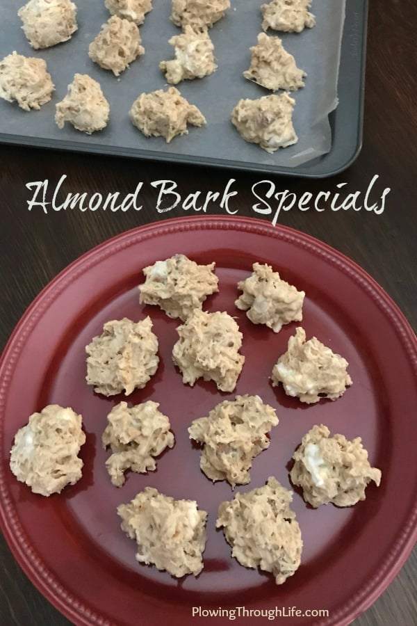 These Almond Bark Specials on a plate made of white almond bark, peanut butter, marshmallows, crispy rice cereal and peanuts make a great snack or dessert