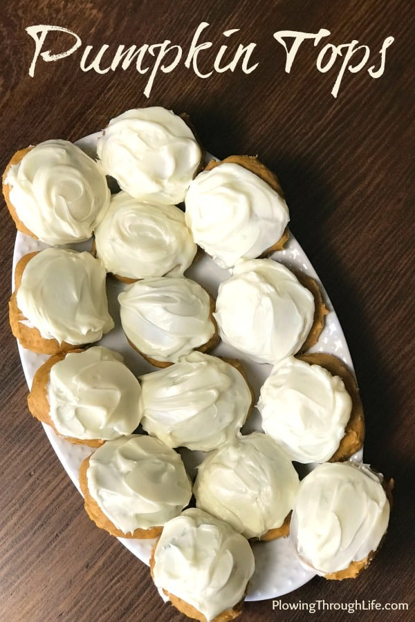 Serving tray of pumpkin cookies with cream cheese icing on wooden table
