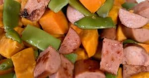 Close up view of smoked sausage, sweet potatoes and green beans