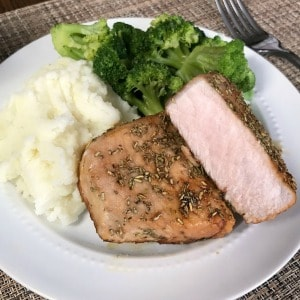 Pork Chops with Brown Sugar, Garlic & Rosemary on a white plate next to mashed potatoes and broccoli