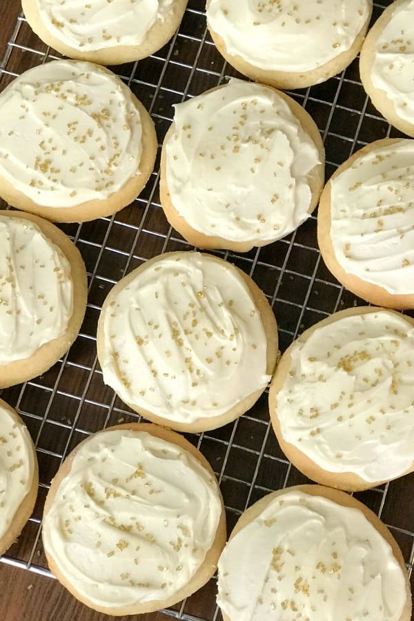 These Sour Cream Cookies are moist, fluffy and simply the best cut out cookies with homemade icing and gold sprinkles on a cooling rack
