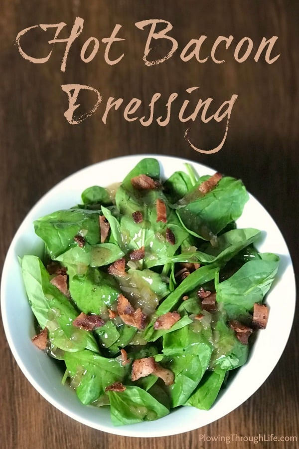 White bowl of spinach covered with hot bacon dressing on a wooden table