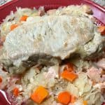 Pork chops and sauerkraut with bacon and carrots on a plate