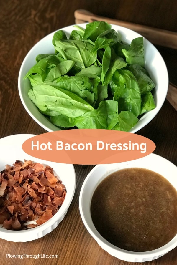Three bowls filled with spinach, bacon and hot bacon dressing on a wooden table