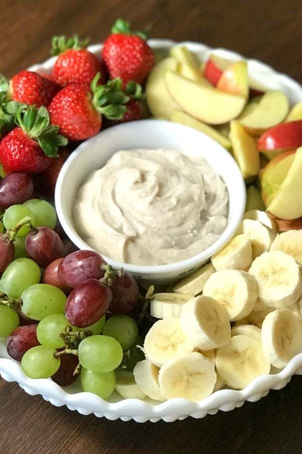 Fruit trays arrangement with grapes, strawberries, apples, bananas and dip for big parties and potlucks.
