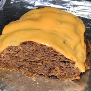 American cheese and bacon covered Crock Pot Cheeseburger Meat Loaf on a foil covered baking sheet