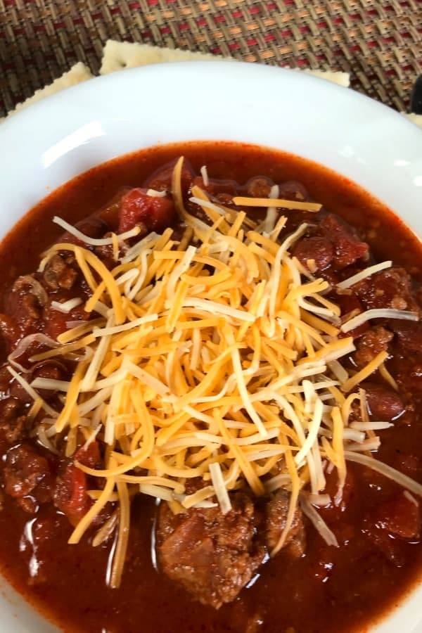 Bowl of meaty Chili with shredded cheese on top, crackers underneath and sitting on a brown placemat