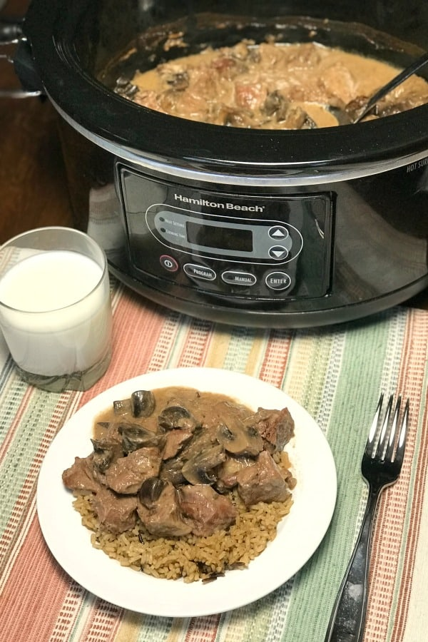 Plate of Crock Pot Stew Meat and Mushrooms in Wine Sauce over rice in front of slow cooker with rest of recipe in it.