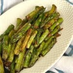 Sautéed Asian Asparagus on a serving plate on a white and blue plaid towel