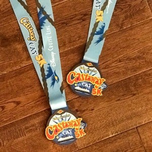Castaway Cay 5K medals on a wood floor