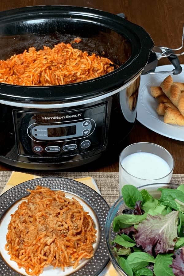 Plate Crock Pot Spaghetti next to crock pot, salad, glass of milk & breadsticks
