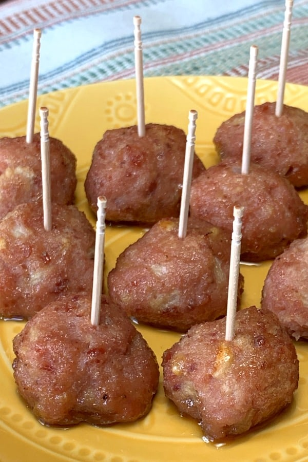 Ham Balls with toothpicks for a party appetizer on a yellow plate