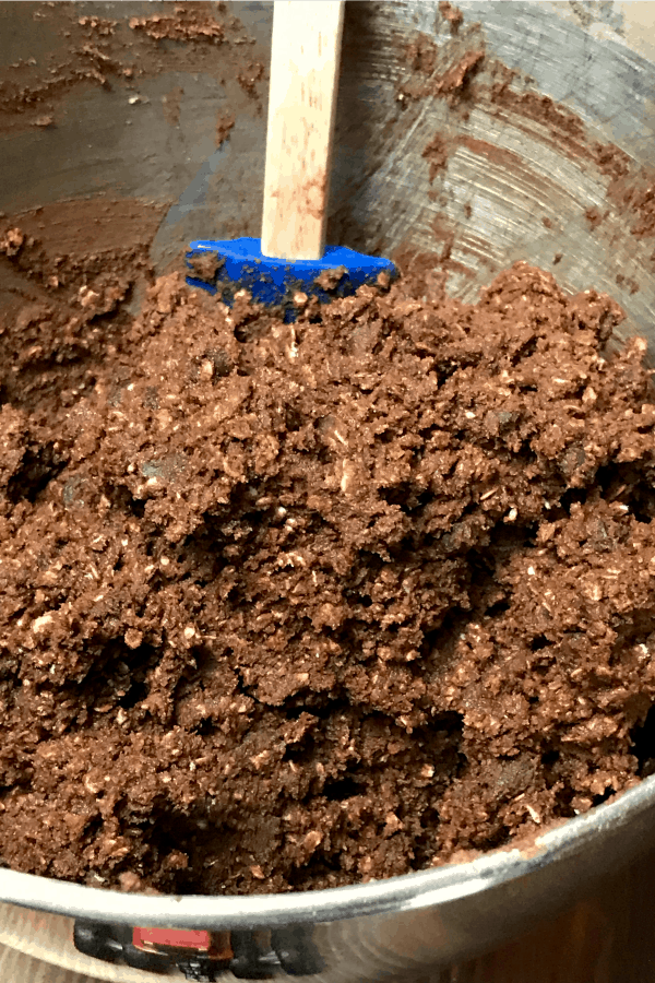 Chocolate oatmeal cookie dough in mixing bowl with spatula