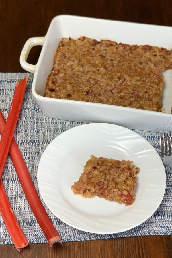 Piece of Farmhouse Rhubarb Crunch on a plate next to full pan with stalks of rhubarb nearby