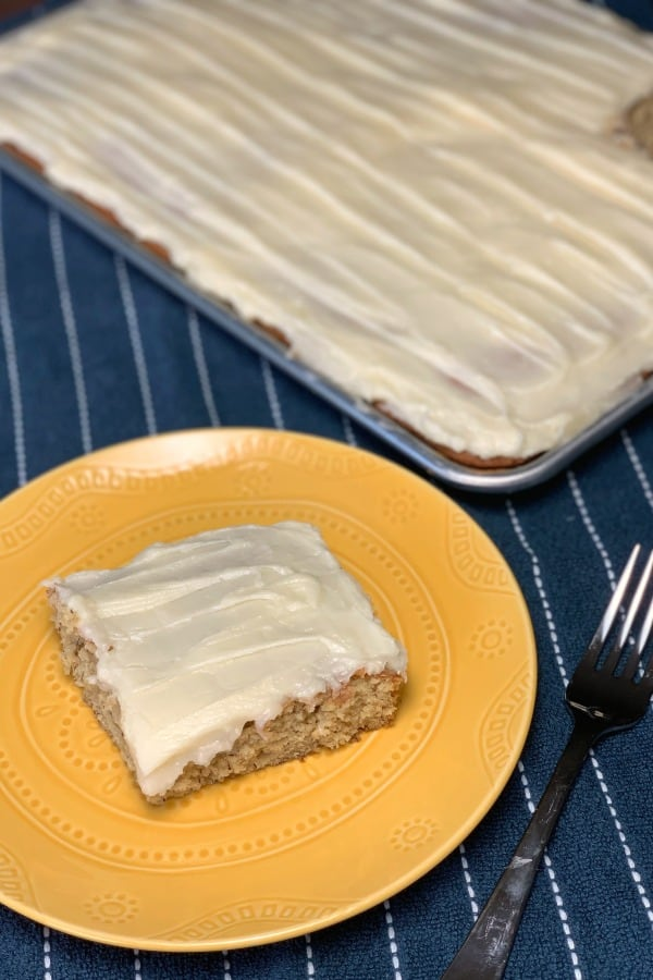 Square Frosted Banana Bar on a yellow plate on a blue dish towel next to baking sheet of banana bars with cream cheese icing!