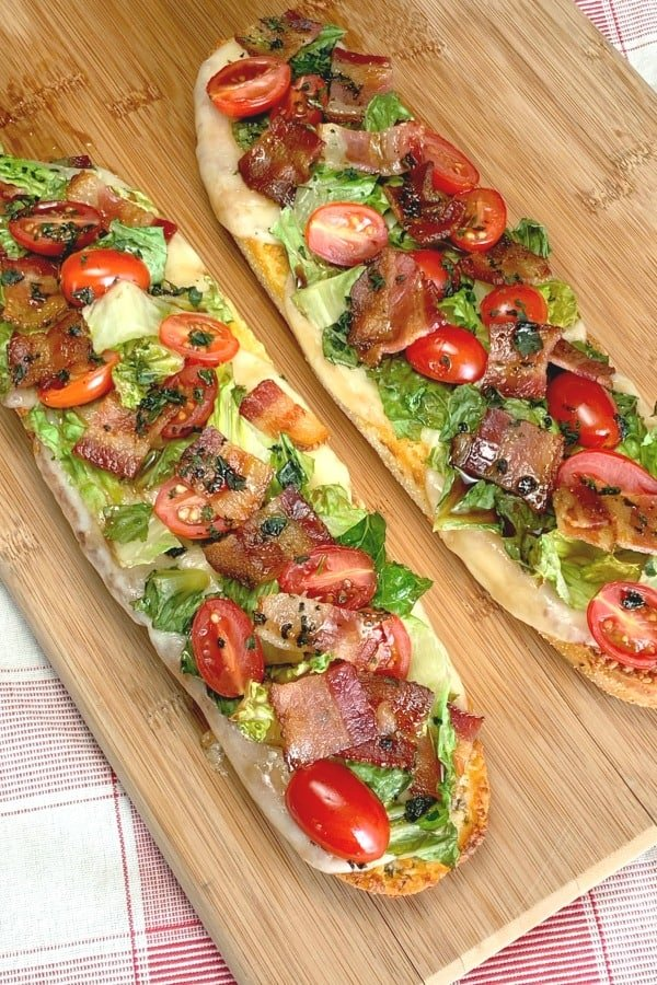 BLT without mayonnaise an Open-Faced Italian BLT with balsamic glaze on garlic bread on wooden cutting board