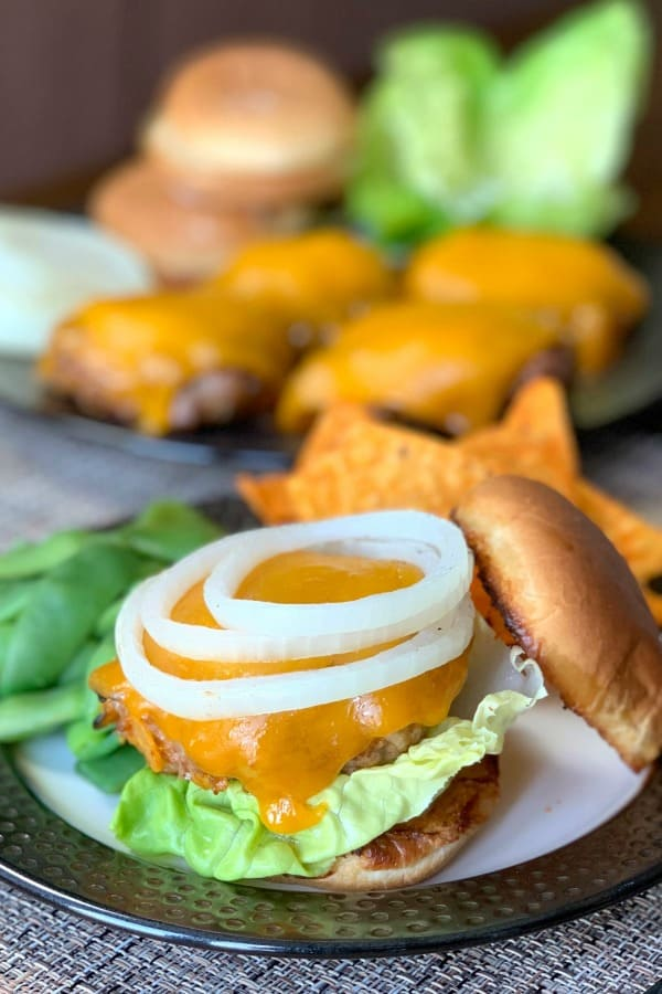 Grilled Loaded Taco Burgers with toasted bun, lettuce, onion and Doritos