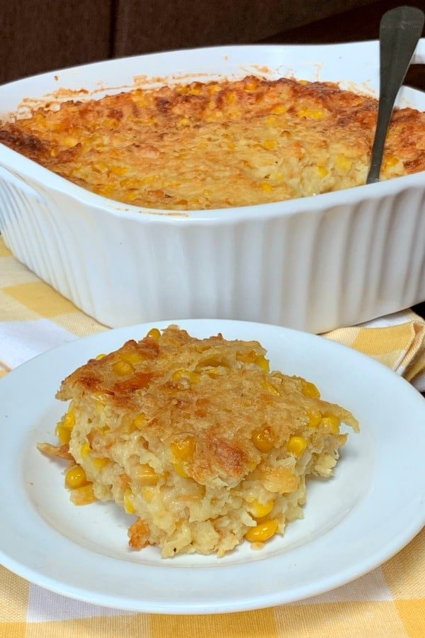 Scalloped Corn corn casserole made with evaporated milk on a white plate next to casserole dish.