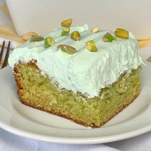 Piece of pistachio pudding cake with cool whip frosting