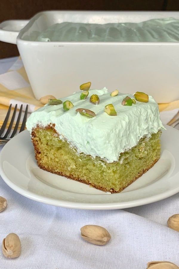 Moist piece of pistachio cake on white plate in front of white 9x13 baking dish