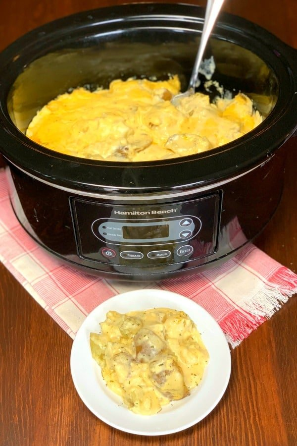 Easy Creamy Crock Pot Potatoes on a plate next to crock pot full.