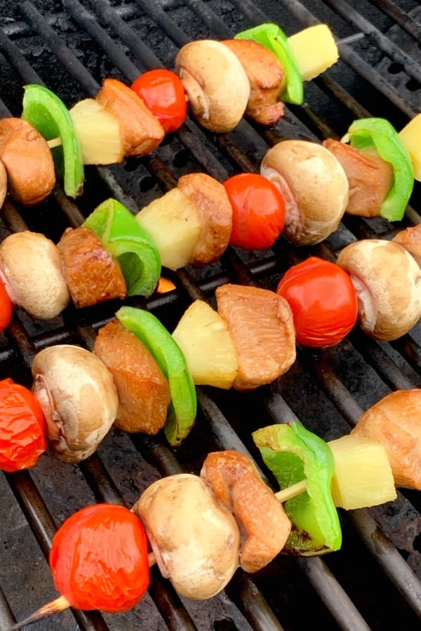 Chicken skewers or kabobs with vegetables and pineapple on grill