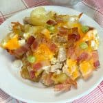 chicken and potato casserole topped with cheese, bacon and green onions