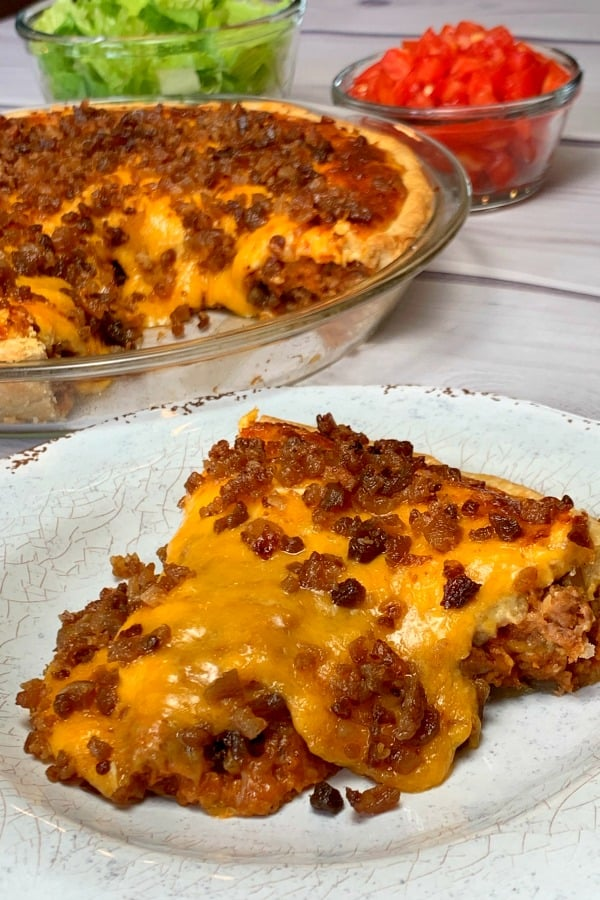 Slice of cheeseburger pie in a pie crust loaded with cheese and bacon