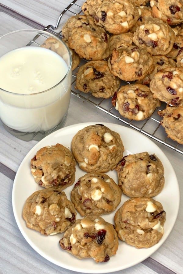 Mew Loaded White Chocolate Cranberry Oatmeal Cookies on a white plate and baking rack next to a glass of milk