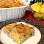 Farmhouse Egg and Sausage Bake on a plate next to casserole dish and garnished with fresh fruit