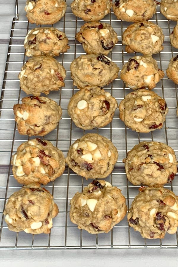 Delicious oatmeal cookie with white chocolate chips and cranberries, freshly baked on a baking rack
