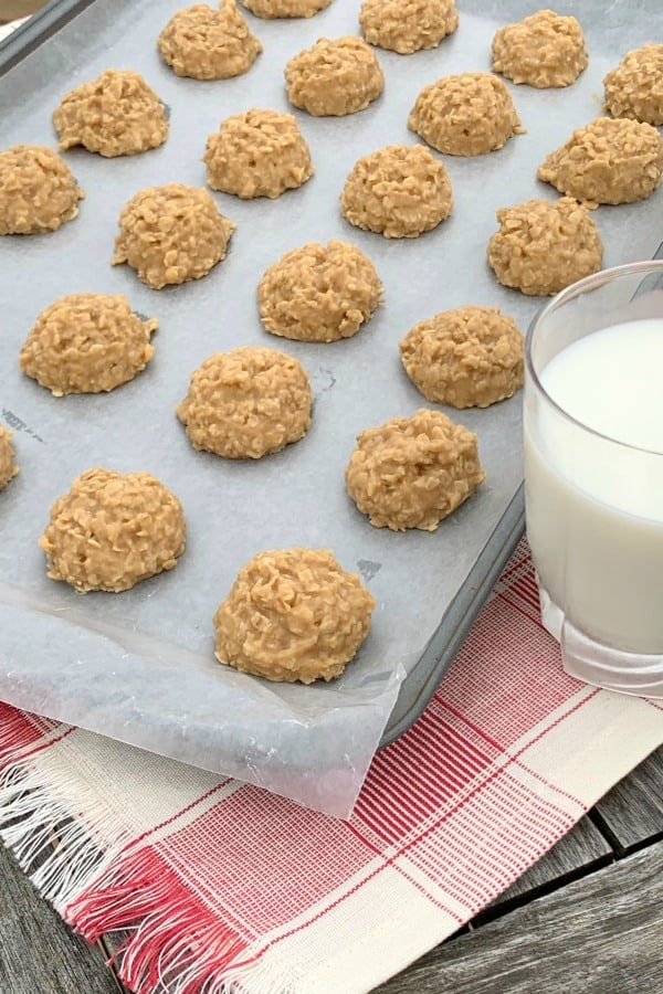 Sheet of no-bake peanut butter drop cookies with a glass of milk on red plaid napkin
