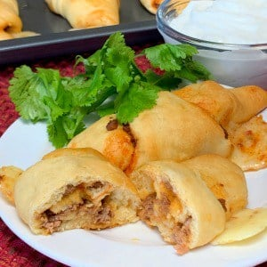Easy Taco Crescents on a plate and cut in half with cheese and taco meat