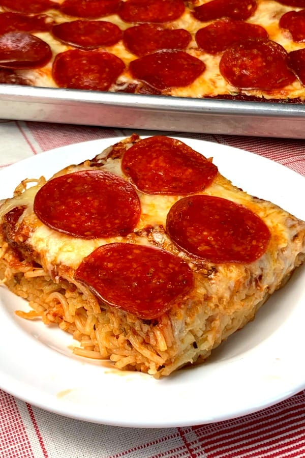piece of spaghetti pizza on a plate next to dish of pizza